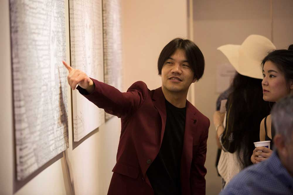 Artist Hayato Takano explaining to guest how he creates his unique masterpiece.